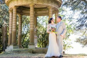 Le couple pose devant un ancien belvédère. Les mariés se regardent tendrement et échange un sourire