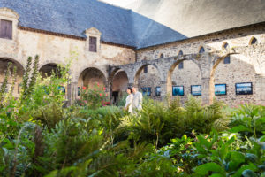 Les mariés sont debout au milieu des végétaux entouré des arches du cloître de l'Abbaye de Léhon