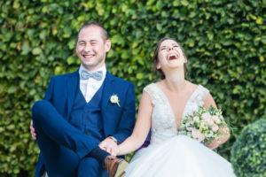 Les mariés sont assis devant une haie bien verte. Ils écoutent le discours de leur proche et ne peuvent s'empêcher d'éclater de rire