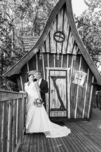Photo en noir et blanc, les mariés posent devant une cabane dans les arbres