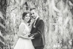 Photos en noir et blanc entre les branches d'un saule pleureur du couple qui regarde l'objectif