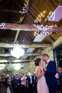 L'ouverture de bal par les mariés sous les jolies lumières de leur salle de réception et sous le regard bienveillant de leurs invités.