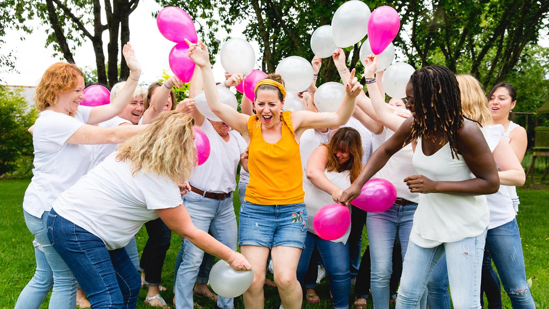Groupe de filles fêtant un anniversaire. Les invitées font une bataille de ballons roses et blanc. La jeune fille dont c'est l'anniversaire est au centre de la photo.