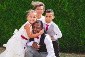 Le marié accroupi se fait câliner par ses enfants avant de rejoindre sa future femme.