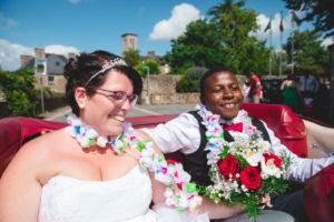 """Les mariés sont assis à l'arrière d'une mustang rouge et sont heureux de se diriger vers la mairie pour se dire """"oui"""""""