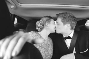 Le couple de marié sorte de la mairie. Ils sont à l'arrière de leur voiture et s'embrassent.