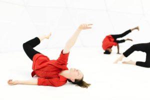 Une danseuse dans un univers blanc habillée en rouge et noir, évolue au sol