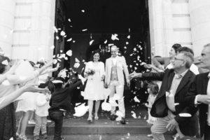Photo en noir et blanc d'une sortie des mariés de la mairie sous une pluie de pétales blancs