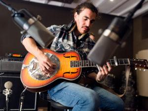 Photo couleur d'un guitariste en train d'enregister en studio