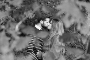 Photo en noir et blanc de deux amoureux qui s'embrassent discrètement cachés derrière les branches d'un arbre
