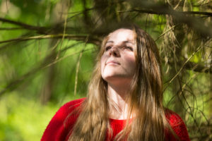 Portrait en couleur d'une jeune fille qui regarde vers la lulière à travers les ombres que créent les branches d'un arbre