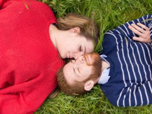 Photos en couleur prise du dessus d'un couple en train de dormir tête contre tête dans l'herbe