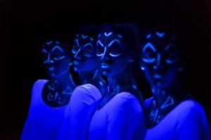 Photos de quatre femmes dans le noir recouvertes de peinture phosphorescente
