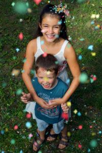 Portrait vertical de deux enfants sous une pluie de confettis