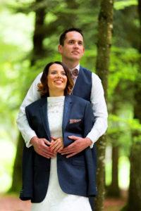 Au milieu des couleurs forestières, les mariés posent. Le marié a prêté sa veste à sa dulcinée pour la protéger du froid.