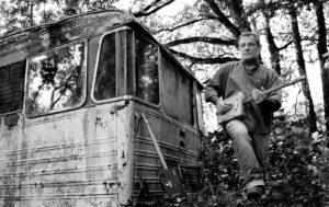 Photo en noir et blanc d'un musicien à la cigar box guitar à côté d'une vielle caravane