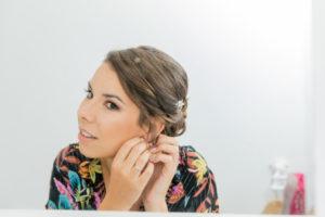 Dans un miroir, la mariée met ses boucles d'oreilles