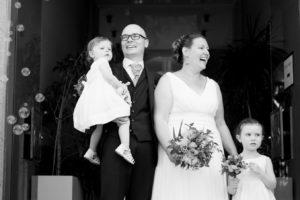 Photo en noir et blanc, Le couple de mariés sort de la mairie et sont rejoint par leurs deux petites filles. Les sourires révèlent leur bonheur