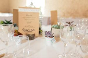 Photo de détail d'une table de réception avec sa jolie décoration et la présentation du menu