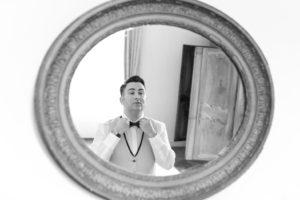 Le marié se regarde dans le miroir et ajuste son nœud papillon avant de retrouver sa future épouse