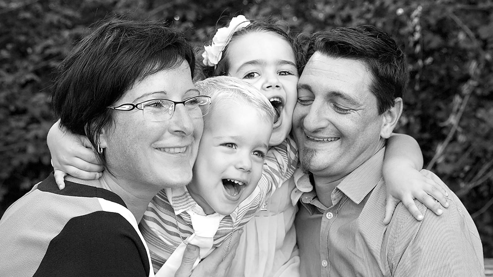Deux enfants et leurs parents rient de bon cœur en étant serrés les uns contre les autres. Photographie en noir et blanc.