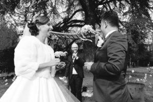 Le couple flou en premier plan, rigole et regarde leur ami qui officie lors de leur cérémonie laïque.