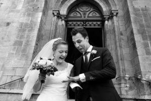 Photo en noir et blanc à la sortie de l'église où les mariés s'extasient devant leurs nouvelles alliances