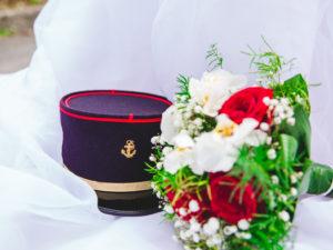 Sur fond de robe de mariée, le bouquet de fleur et le képi du marié se mélangent