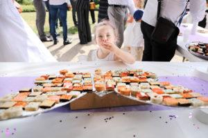 Une petite fille se sert au buffet du vin d'honneur et à l'air de se régaler !