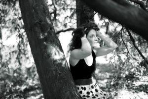Portrait en noir et blanc d'un jeune fille assise sur un arbre