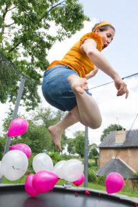 Une future mariée exprime sa joie lors de son enterrement de vie de jeune fille en sautant sur un trampoline rempli de ballons
