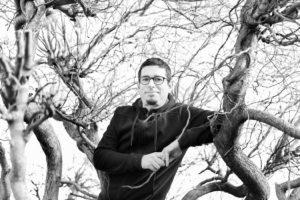 Portrait en noir et blanc d'un dessinateur au milieu des branches dénuées de feuilles